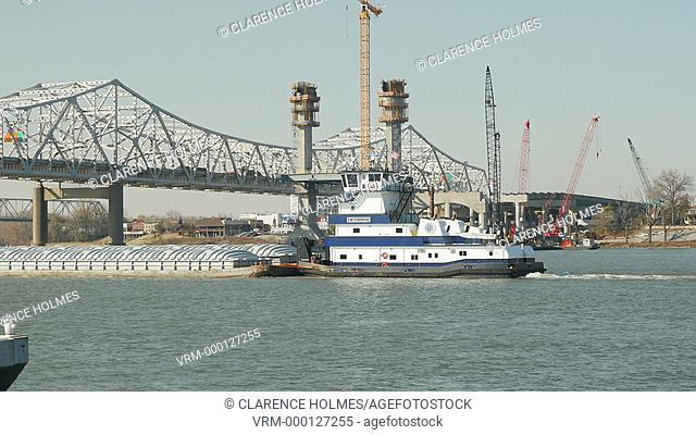 LOUISVILLE, KY - NOVEMBER 20: C&B Marine towboat Enterprise pushes a barge on the Ohio River toward the I-65 bridge construction project and Kennedy Bridge on...
