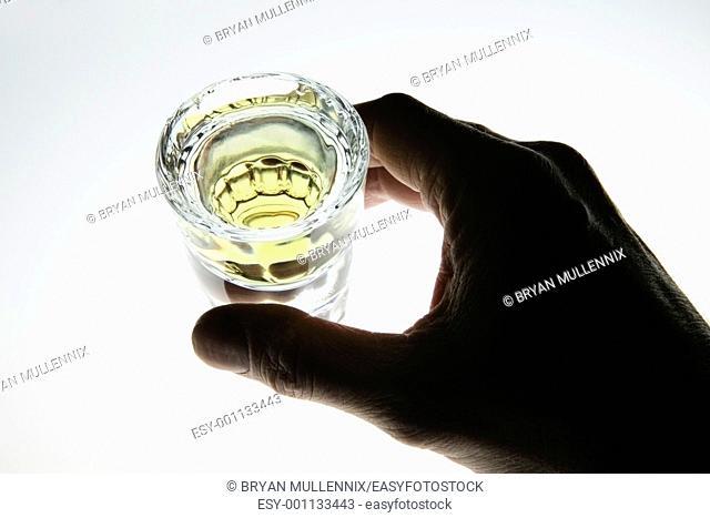 Hand around shot glass of liquor, tequila