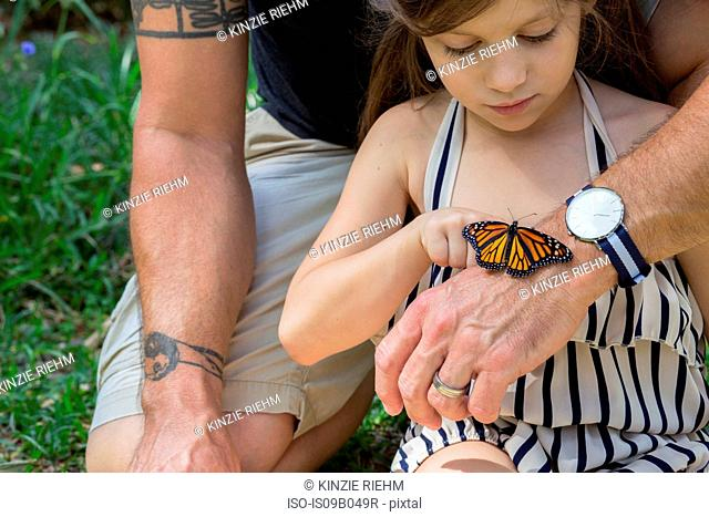 Father and daughter looking at monarch butterfly