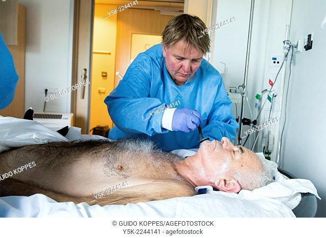 Tilburg, Netherlands. Male orthopedic patient, recovering in a hospital sand bed to prevent decubitus, is nursed by a female nurse