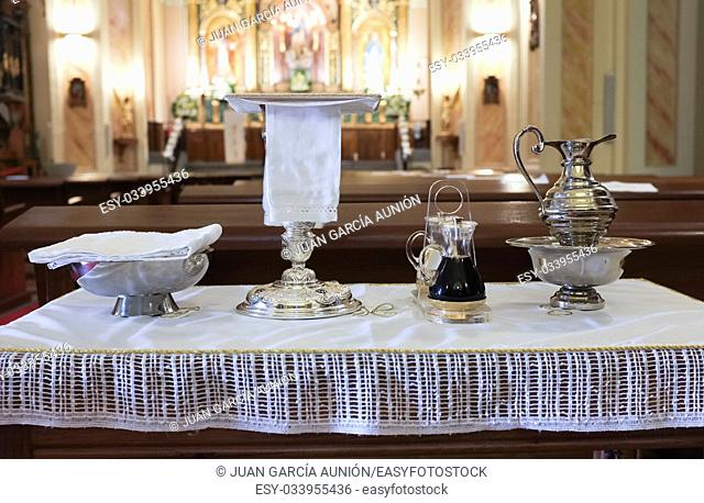 Catholic liturgical objects displayed over table at church. Chalice, communion wafers, wine, water, ewer and basin