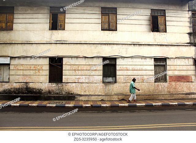 PUNE, MAHARASHTRA, INDIA, October 2018, Man walking past an old house
