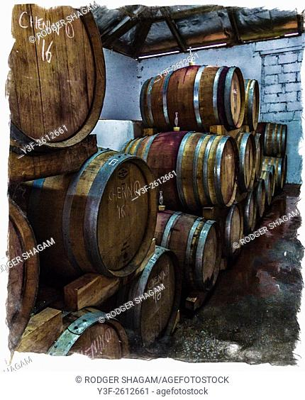 Wine maturing in barrels in a wine cellar. Grunge with border. Western Cape Province, South Africa