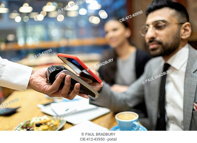 Businessman in cafe paying with smart phone contactless payment