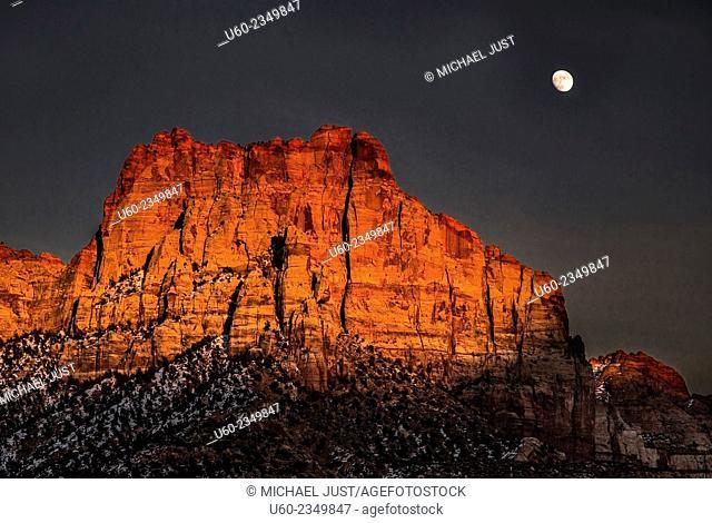A bright rising moon makes an appearance at Zion National Park, Utah
