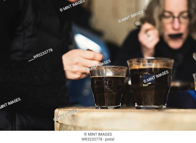 Close up of two glasses with coffee standing on wooden table, people in background