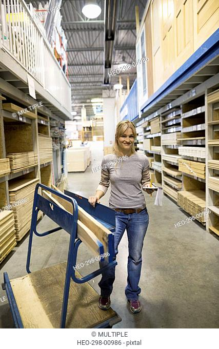 Portrait smiling woman with notepad shopping for wood in home improvement store