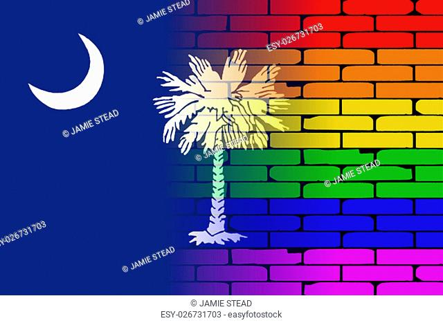 A well worn wall painted with a LGBT rainbow with the South Carolina state flag