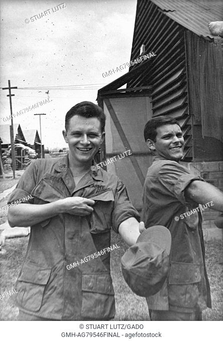 A photograph of two United States Army soldiers wearing their jungle jackets, both men are smiling and the one of the left is holding out his fatigue cap
