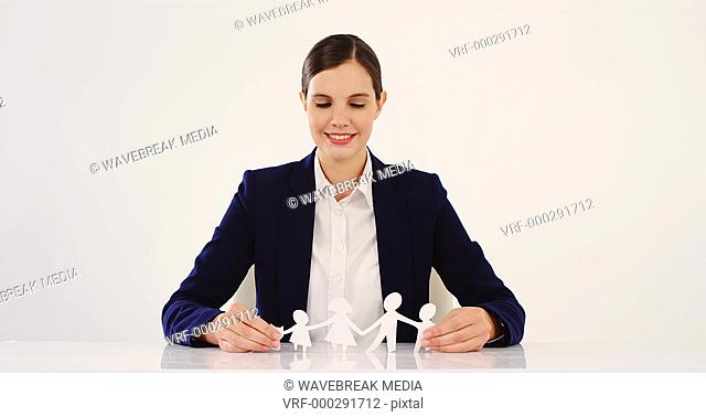 Businesswoman holding paper cut out of a family