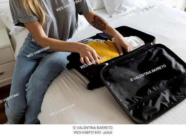 Close-up of woman sitting on bed with suitcase
