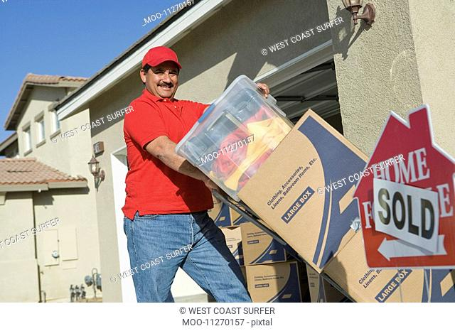 Portrait of mid-adult man moving into house