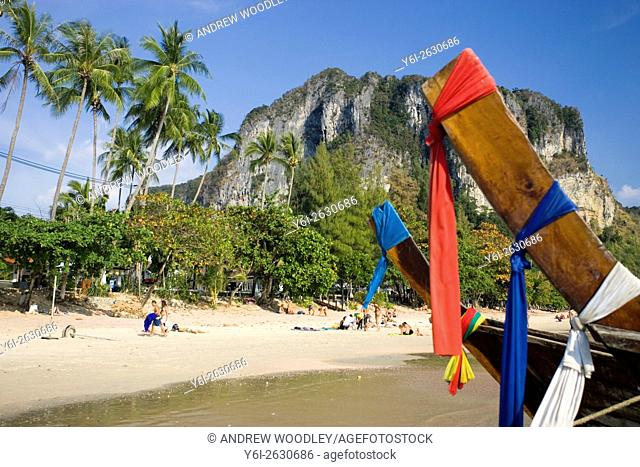 Longtail traditional boats with color prayer scarves pulled up at popular beach Ao Nang Thailand