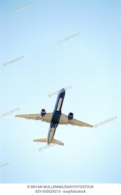Commercial airplane flying overhead against blue sky, taking off