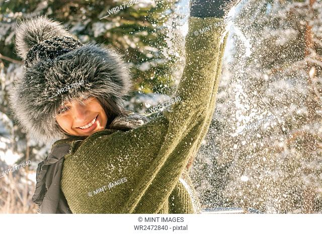 Smiling woman with a furry hat playing in the snow in winter
