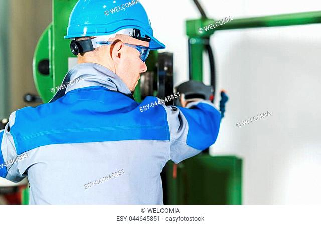 Professional Heavy Duty Machinery Operator. Caucasian Metalworking Industry Worker in Blue Hard Hat in Front of Machine Console. Industrial Theme