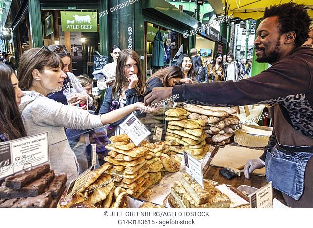 England, London, South Bank Southwark, Borough Market, vendors stalls, Olivier's bakery, pastries, brownies, Black, man, woman, buying, selling, giving change