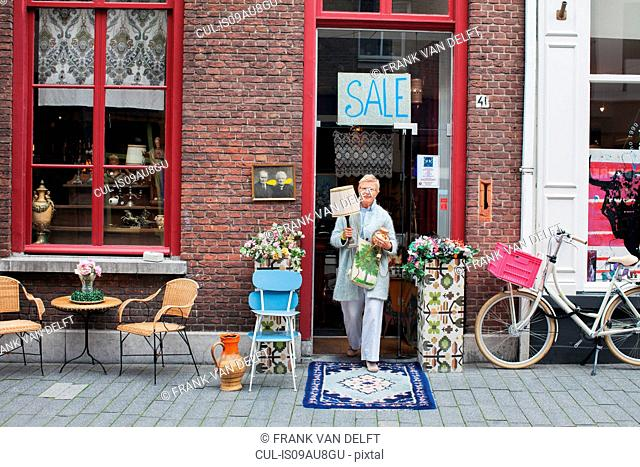 Mature female customer carrying lamp outside vintage shop