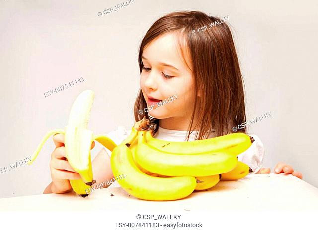 A young girl is eating a delicious looking yellow banana. She looks like she is enjoying herself