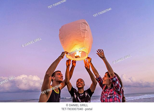 Young people with illuminated lantern on beach