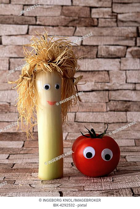 Leek and tomato with faces, symbolic picture for healthy vegetables