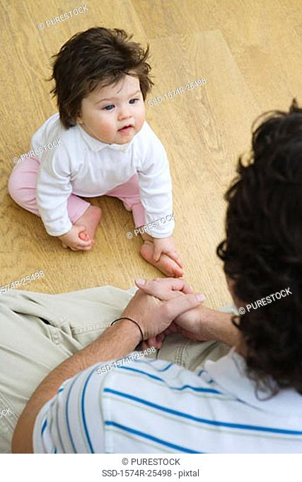 High angle view of a baby girl sitting in front of her father