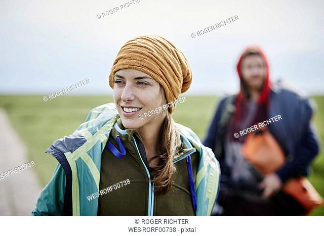 Smiling woman with man in background on a trip