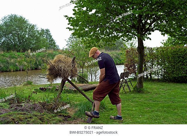 man in Knickerbockers burrowing in a garden , Germany, Lower Saxony, Westgrossefehn