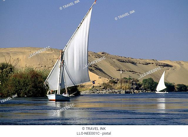 Two Feluccas on a Calm River Nile with Dunes in Background  Aswan, Egypt