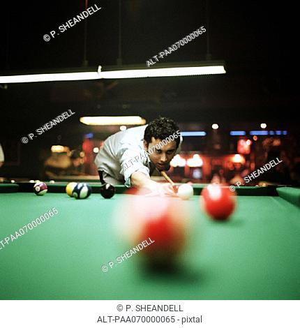 Young man shooting pool, billiard ball blurred in foreground
