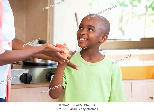 Little boy taking an apple from his mother