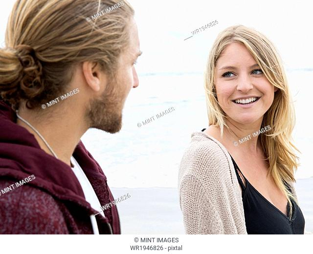 Young man and young woman on a beach, looking at each other, smiling