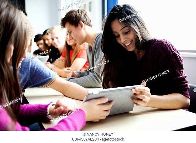 Teenage schoolgirls sitting at desk using digital tablet