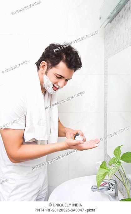 Man shaving his face in the bathroom