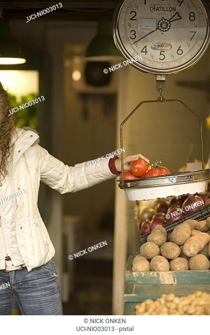 Young woman weighing tomatoes