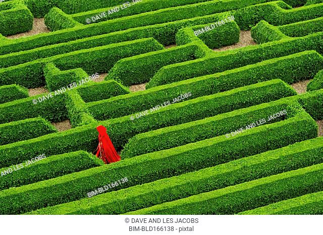 Aerial view of Caucasian woman in red cloak walking in hedge maze