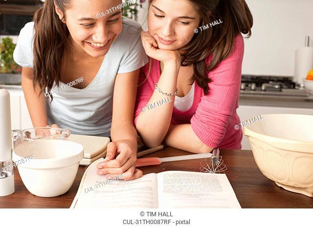 teenage girls looking at recipe in kitchen