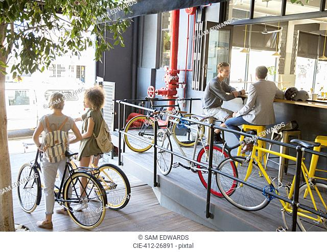 People with bicycles at urban outdoor cafe