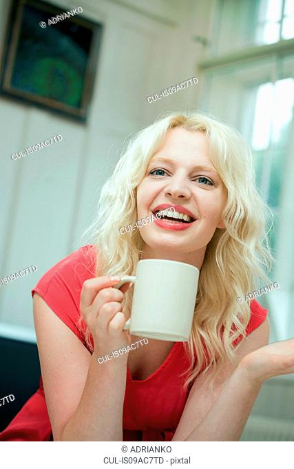 Young woman in conversation, holding a hot drink