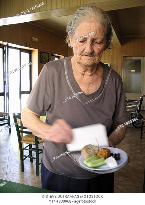 Old lady serving a simple Meze, Galatas Village Kafeneio, Crete, Greece
