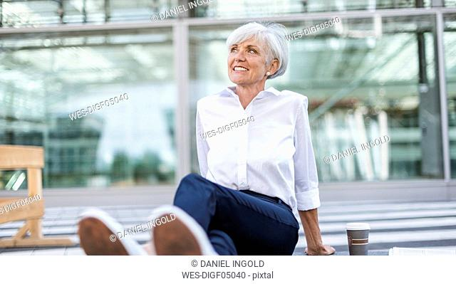 Smiling senior businesswoman sitting outside looking around