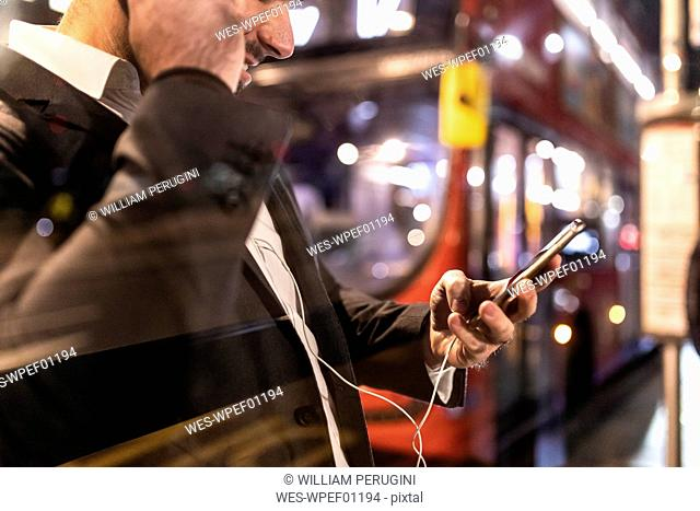 UK, London, businessman with cell phone and earbuds at the bus station by night