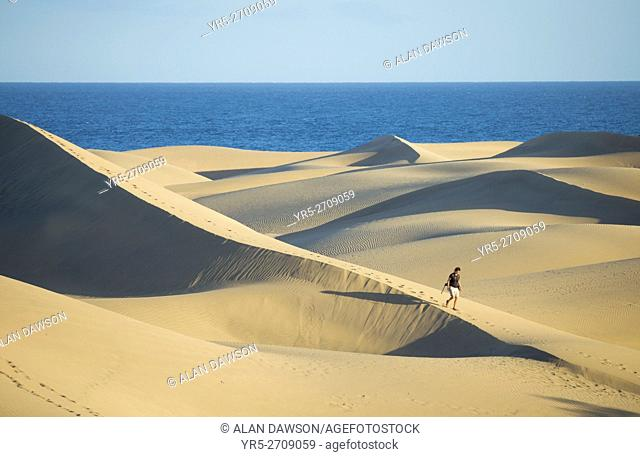 Female hiker with backpack walking through the vast expanse of sand dunes at Maspalomas, Gran Canaria, Canary Islands, Spain, Europe. Model released