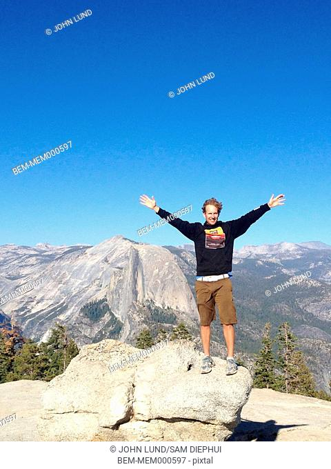 Caucasian man cheering on mountaintop, Yosemite, California, United States