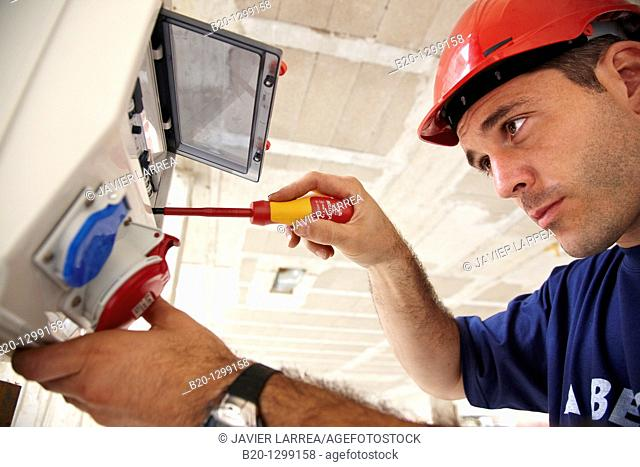 Worker using screwdriver in construction site, fuse box