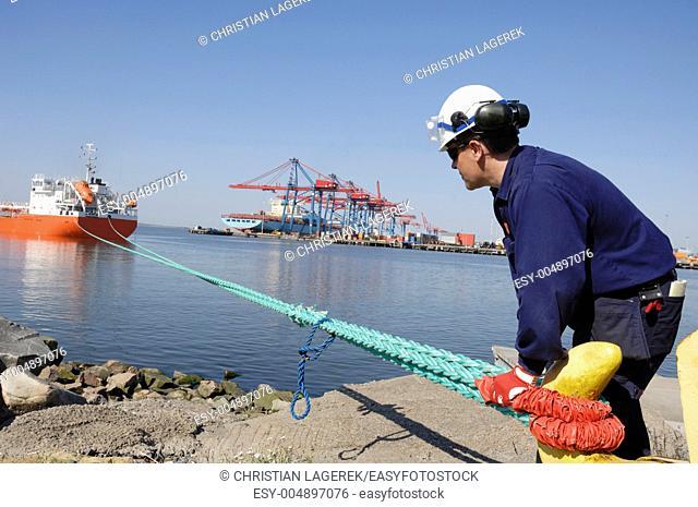 dock worker moring ship large container port in background. Stockholm. Sweden