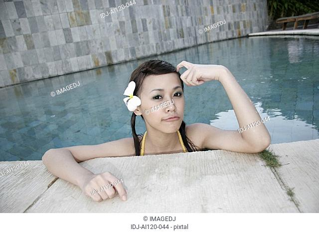 Portrait of a teenage girl leaning near swimming pool