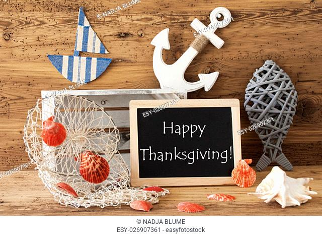 Blackboard With Nautical Summer Decoration And Wooden Background. English Text Happy Thanksgiving. Fish, Anchor, Shells And Fishnet For Maritime Contex