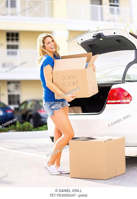 Young woman carrying box from car into her new house