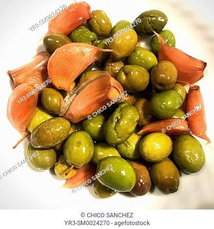 Olives and garlic in a yellow plate in Prado del Rey, Sierra de Cadiz, Andalusia, Spain